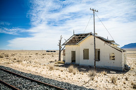 Delapidated abandoned building next to old rusted railway tracks in the desert.