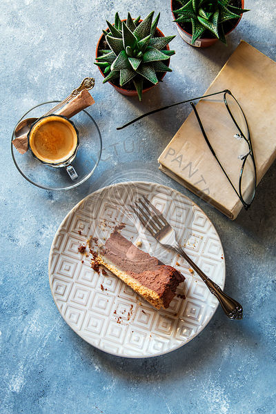 A slice of chocolate cheesecake on a plate, cup of cofee, old book, glasses and succulent plants on background