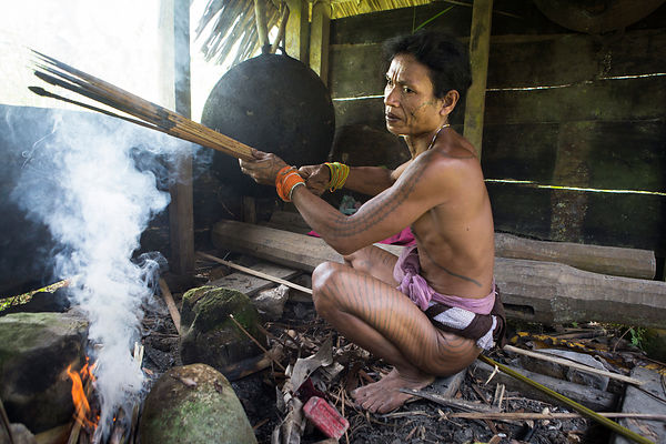 Amantari, 39, smokes his arrows after applying poison before going hunting, Pulau Siberut, Sumatra, Indonesia