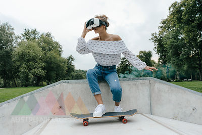 Young woman with skateboard wearing VR glasses in a skatepark