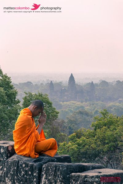 Monk praying in front of Angkor Wat temples, Cambodia