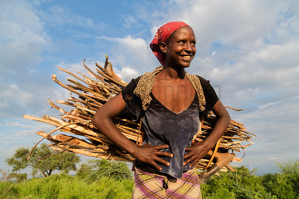 Woman Carrying a Bundle of Firewood Sticks at Dusk