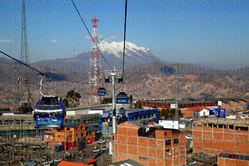 Blue Line cable car cabins descending to terminal in La Ceja, Mt Illimani in background, El Alto, Bolivia