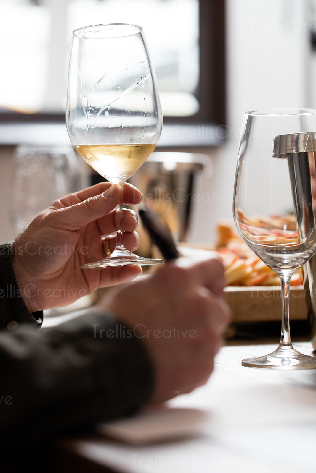 Close-up of a person holding wine glass at a tasting event taking notes