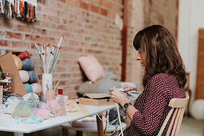 Woman sitting at table knitting