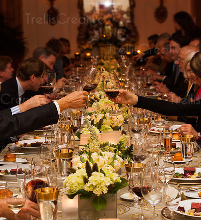 A man and woman toast glasses of red wine across an elegantly decorated table