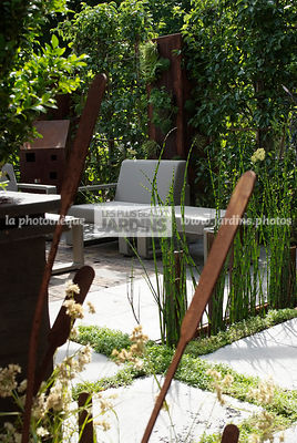Terrasse contemporaine. Mobilier de jardin (collection Kama d'Ego Paris). Décoration de jardin en Corten par Eric Ferber. Pay...