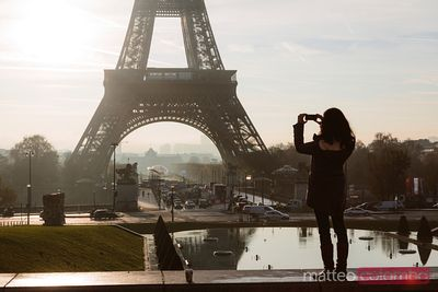 Femme prenant une photo de la tour Eiffel, Paris, France