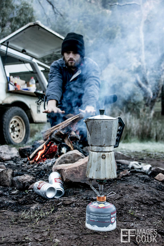 Man Warming His Hands On A Campfire While Waiting For The Coffee To Brew