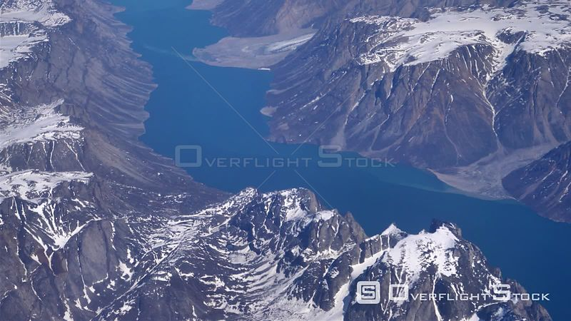 Deep blue ocean fjord surrounded by high snowy mountains, Greenland