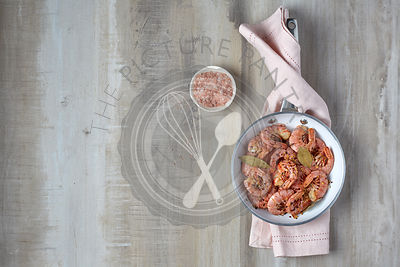 Cooked red shrimp on a light background. Prepared in a frying pan
