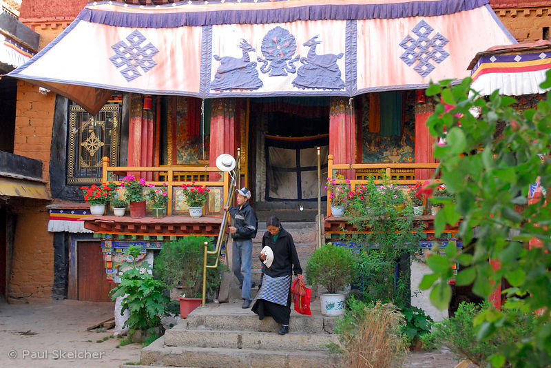 Tibetan Buddhists walk down the steps at Meru Sarpa Monastery, Lhasa, Tibet, China.