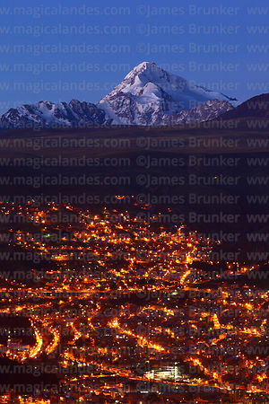 City lights on outskirts of La Paz and Mt Huayna Potosí at sunset, Bolivia