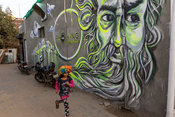 A child dressed in a colourful wig from a nearby village runs past graffiti in Champa Gali
