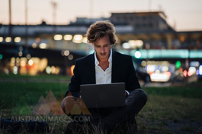 Businessman sitting on meadow at dusk using laptop