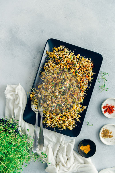 Spicy sprouted lentils with corn served on a black rectangular plate with a spoon and a fork on the side.
