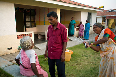 India - Cuddalore - Meena, 65 pretends to hit a male nurse with a crutch.