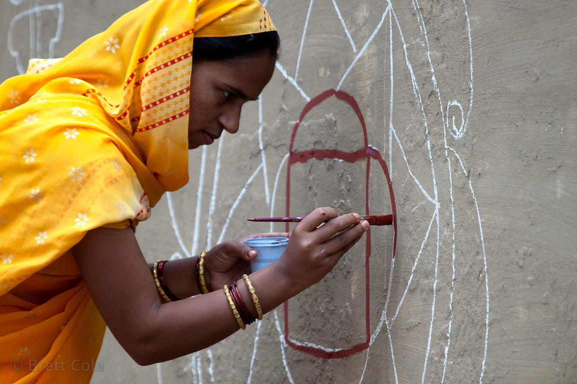 A woman paints a mural at the stadium in Pushkar during the 2010 camel fair, Rajasthan, India