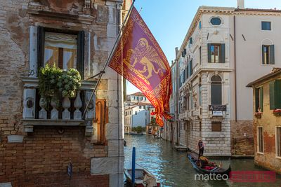 Gondola passing on a canal with venetian flag, Venice