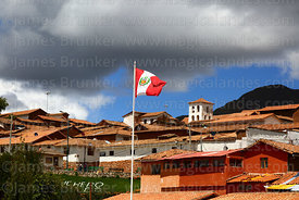 Peruvian flag, rooftops and church tower in Chinchero village, Cusco Region, Peru