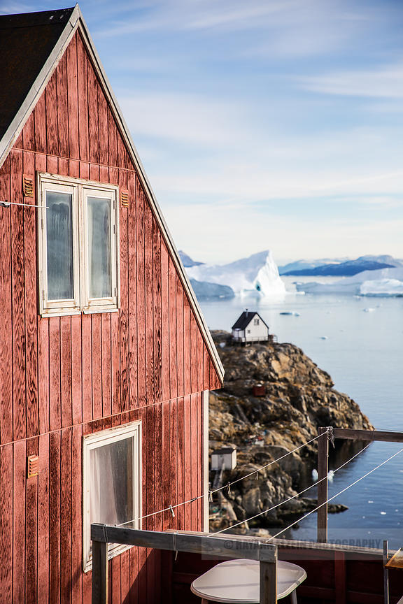 A typical Greenlandic wooden house with beautiful icebergs in the fjord in the background