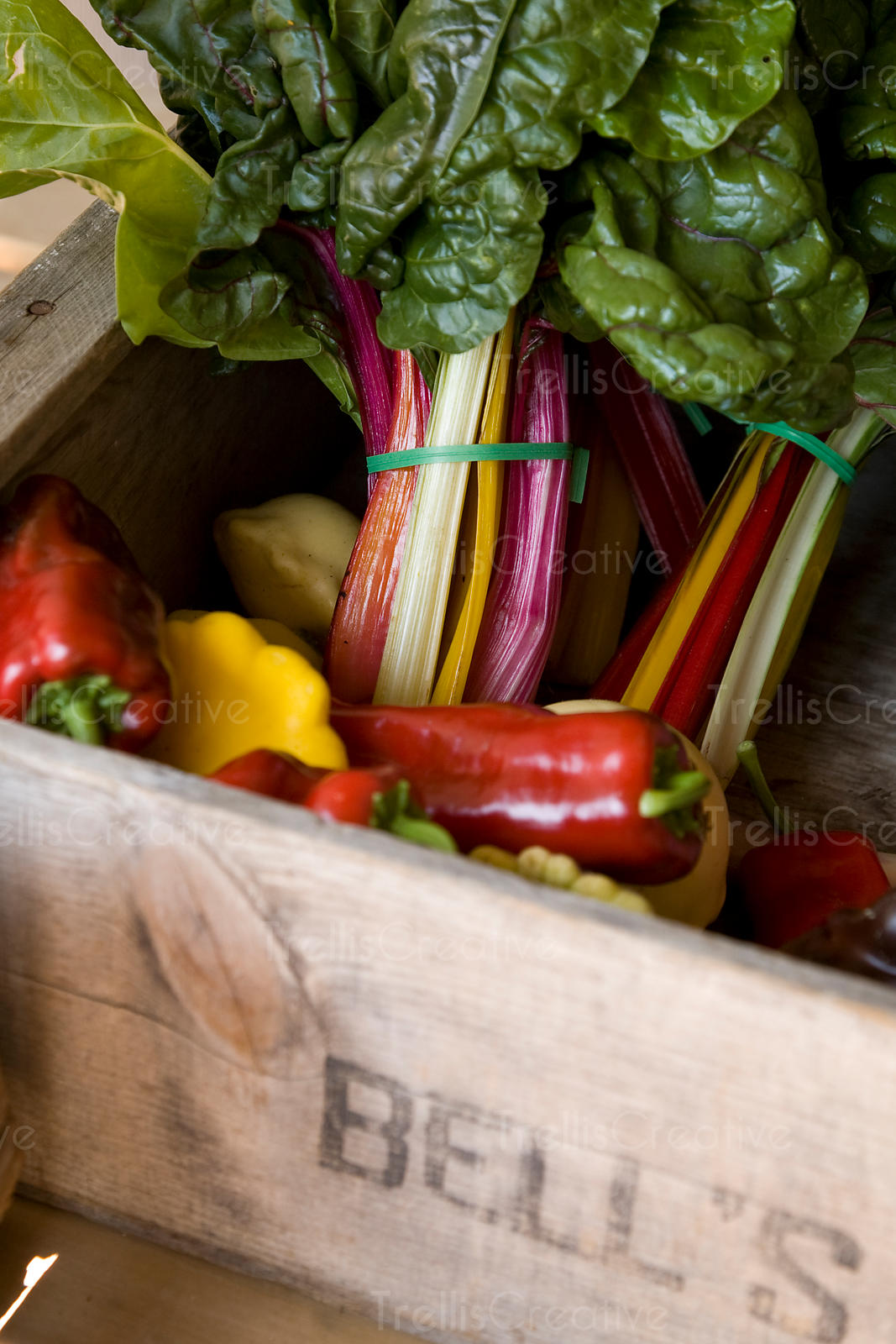 Colorful swiss chard and bell peppers in a wooden crate