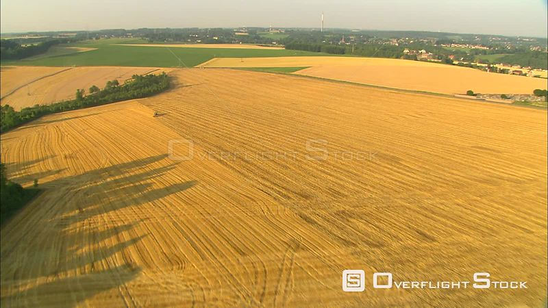 High view of Belgian farmlands and a golden field being mowed