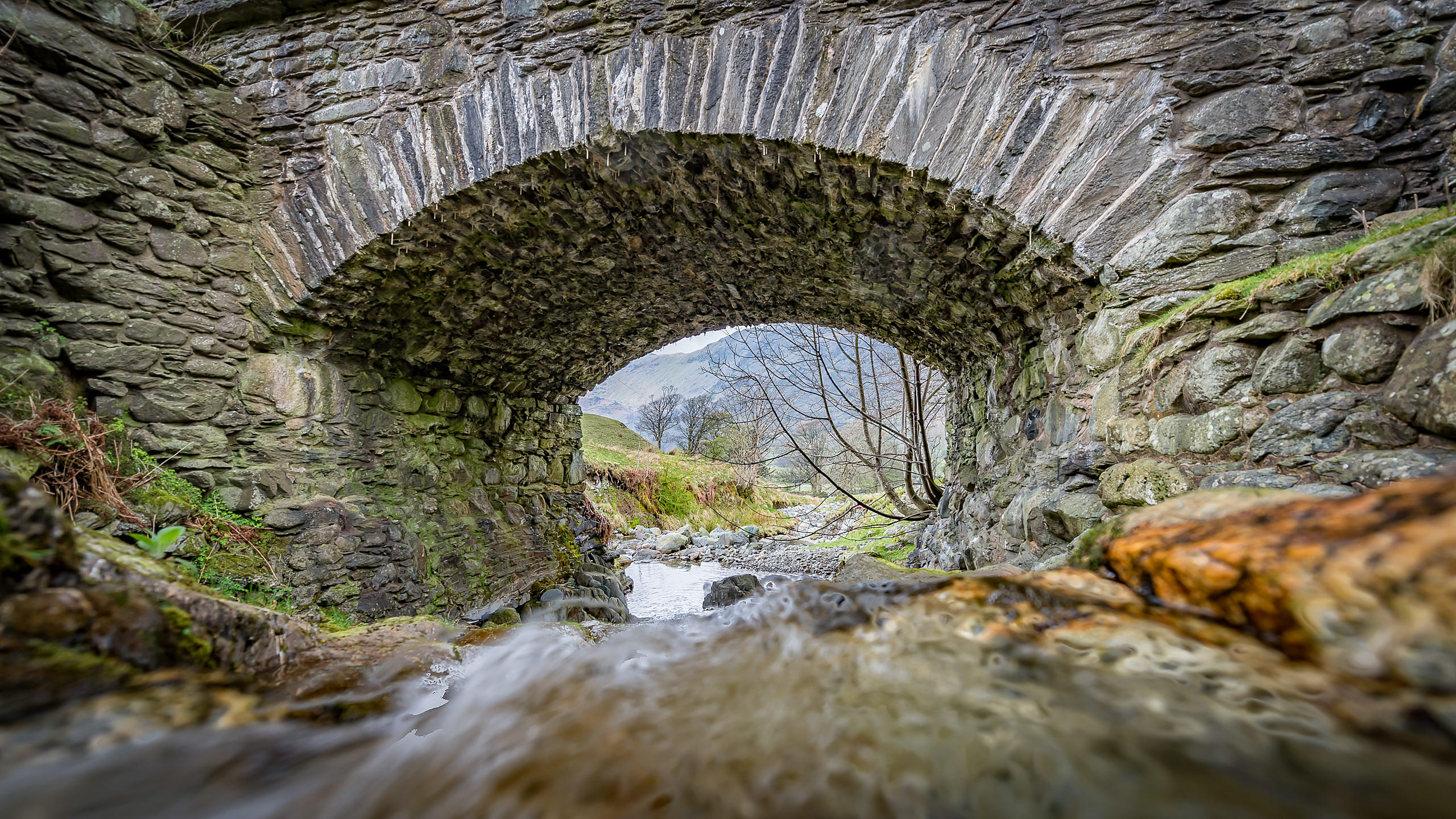Low Shot of Waterfall Under Drystone Bridge in Kirkstone Pass, in the Lake District