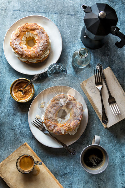 French paris-brest pastries ,coffee mugs and a glass with water on the table