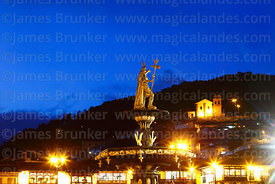Statue of the Inca Pachacuti Inca Yupanqui or Pachacutec on fountain at twilight, San Cristobal church in background, Plaza d...
