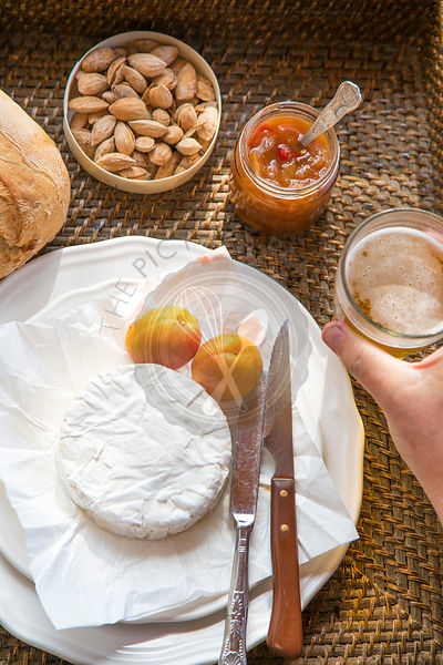 camembert cheese with apricots, apricot chutney, almonds, hand holding beer, set on woven tray