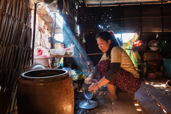 Woman Cleaning Pots in her Kitchen.