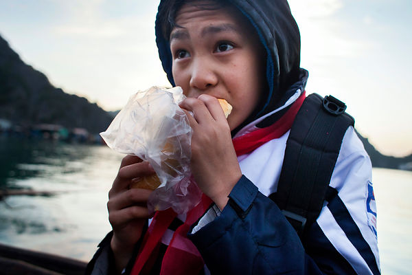 Tué , 12 ans, mange un sandwich en  partant à l'école en bateau, Baie de Lan Ha, Vietnam / Tué, 12 years old, is eating a sandwich while going to school by boat, Lan Ha Bay, Vietnam