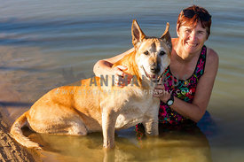 Large dog sitting in river with female adult cuddling him.