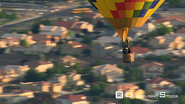 Close mid-air view of passengers in hot air balloon basket with Albuquerque suburbs below.