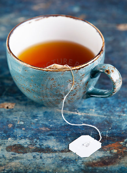 Cup of tea with teabag on blue textured background