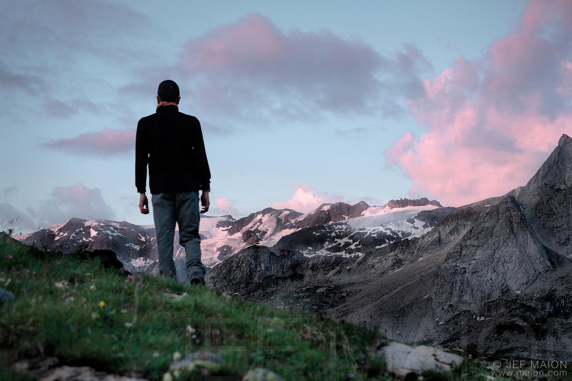 Hiker silhouette against glaciers at sunset