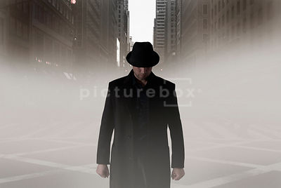 An atmospheric image of a mystery man in a hat walking down a deserted, misty avenue in New York City.