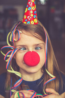 Cross-eyed girl with clown's nose, cap and streamer