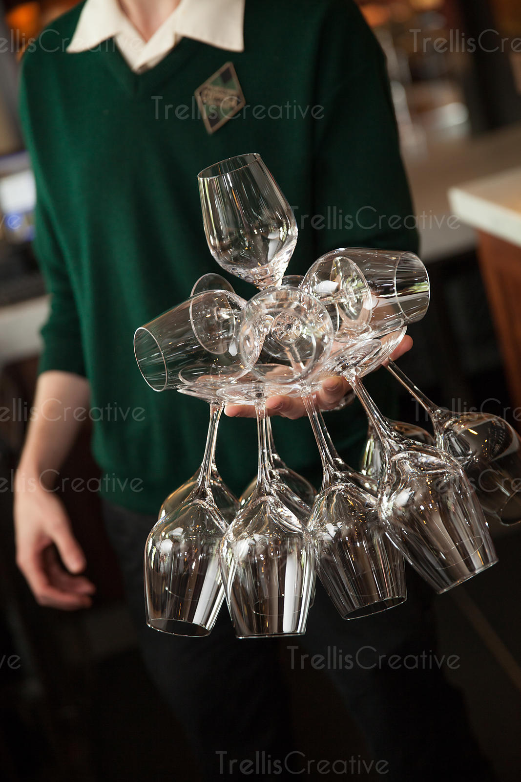 Person balancing a stack of wine glasses in one hand