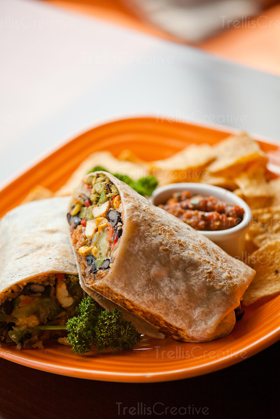 A bean and chicken burrito served with tortilla chips and salsa
