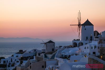 Romantic sunset over the windmills of Oia, Greece, Santorini
