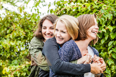 Three female friends hugging in garden