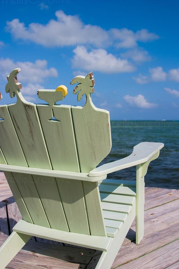 Whitewashed pale green Adirondack chair with martini and palm tree motif on back of chair on weathered section of deck facing...