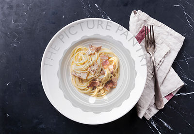 Pasta Carbonara on white plate with parmesan on dark marble background