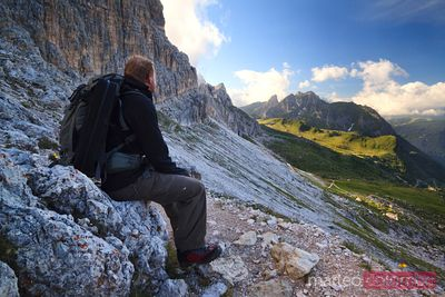 Hiker looking at the mountains Dolomites Italy