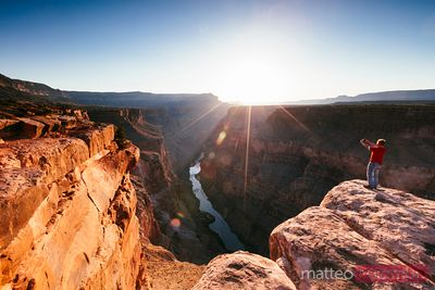 Man on the edge of Grand Canyon at sunrise