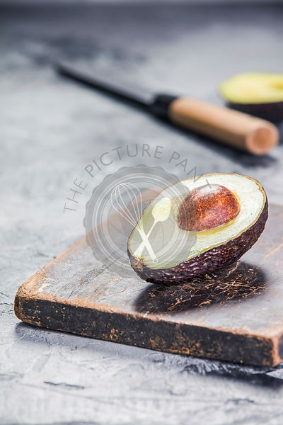 Green ripe avocado and knife on a grey stone background