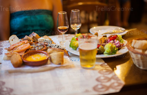 Woman sitting at table with mixed Spanish Tapas