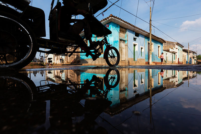 Bicitaxi Reflected in Puddle on Street